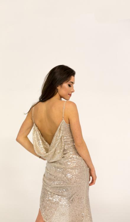 Długa świecąca sukienka w kolorze szampańskim złota z cekinami rozcięcie na nodze z marszczeniami odkryte plecy na sylwestra
